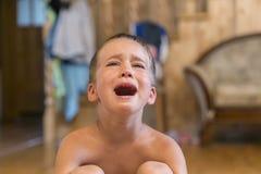 Мальчик сидя на поле, he& x27; осадка и плакать s Ребенок плача сидеть на поле в комнате стоковые фото