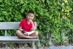 Мальчик сидя на руке деревянной скамьи на его подбородке и держать Стоковые Изображения RF