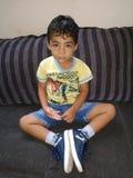 мальчик сидя на софе стоковая фотография rf