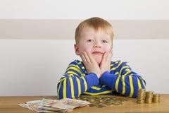Мальчик сидя перед деньгами Стоковое Изображение