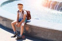 Мальчик сидя фонтаном на солнечный день стоковые фотографии rf