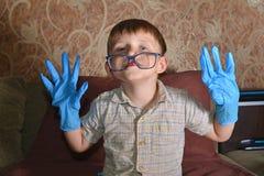 Мальчик сильно эмоциональный в голубых медицинских перчатках показывает различную сторону на камере Стоковое фото RF