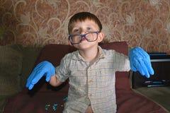 Мальчик сильно эмоциональный в голубых медицинских перчатках показывает различную сторону на камере Стоковое Изображение RF