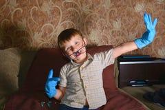Мальчик сильно эмоциональный в голубых медицинских перчатках показывает различную сторону на камере Стоковые Изображения