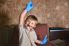 Мальчик сильно эмоциональный в голубых медицинских перчатках показывает различную сторону на камере Стоковые Фото