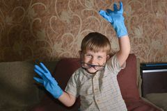 Мальчик сильно эмоциональный в голубых медицинских перчатках показывает различную сторону на камере Стоковые Изображения RF