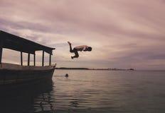 Мальчик скача в море стоковое изображение rf