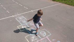 Мальчик скачет играющ классики в улице Вид спереди сток-видео