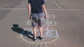 Мальчик скачет играющ классики в улице Ноги конца-вверх акции видеоматериалы