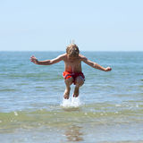 мальчик скачет над волной Стоковое Фото