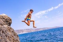 Мальчик скачет от скалы в море на горячий летний день Праздники на пляже Концепция активного туризма стоковое изображение