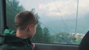 Мальчик смотрит вне окно кабел-крана Красивый ландшафт, горы E lifestyle видеоматериал
