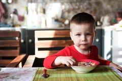 Мальчик смотрит камеру пока ел завтрак стоковое изображение rf