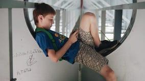Мальчик смотрит телефон сидя под мостом Крутая архитектура Эмоциональные кинематографические съемки сток-видео