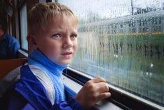 мальчик смотрит унылое окно Стоковые Изображения RF