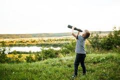 Мальчик смотря в окуляр телескопа Стоковые Фото