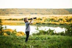 Мальчик смотря в окуляр телескопа Стоковые Изображения RF