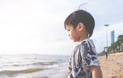 Мальчик смотря на вне к морю на пляже каникул Стоковая Фотография RF