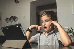Мальчик смотря удивленный смотрящ таблетку дома Ребенок смотря таблетку стоковое фото rf
