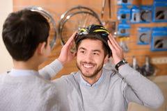 мальчик смотря шлем велосипеда счастливого отца нося стоковое фото