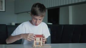 Мальчик собирает деревянную модель дома сидя на таблице видеоматериал