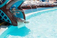 Мальчик сползает на водные горки в бассейн Стоковые Изображения RF