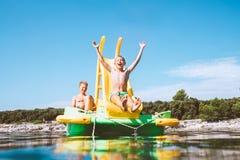Мальчик сползая вниз в морскую воду от плавая катамарана скольжения спортивной площадки по мере того как она наслаждаясь отключен стоковые фото