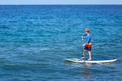 Мальчик стоит вверх paddleboarding стоковое фото
