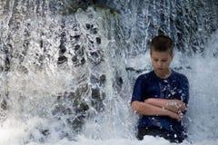 Мальчик стоит в водопаде Стоковое Изображение