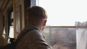 Мальчик стоит на окне поезда и смотрит вне окно на идущих ландшафтах нутряное быстро проходя перемещение поезда Туризм дальше видеоматериал