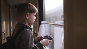 Мальчик стоит на окне поезда с планшетом в его руках нутряное быстро проходя перемещение поезда Туризм каникул, путешествуя мир сток-видео