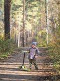 Мальчик стоит со скутером в парке стоковые изображения rf