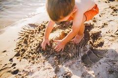 Мальчик строит диаграммы от песка на береге пруда на заходе солнца дня, руки выкапывает вверх песок в хрустящем плане стоковое фото rf