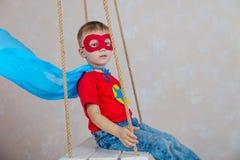 Мальчик супергерой в голубой накидке на качании Стоковое Изображение