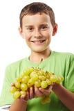 Мальчик с виноградинами Стоковая Фотография