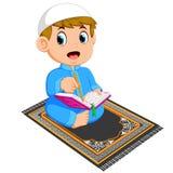 Мальчик с голубым caftan читает Коран al на половике молитве бесплатная иллюстрация