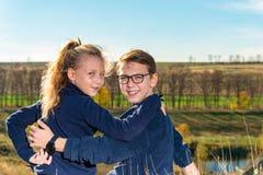 Мальчик с девушкой сидит на скале, 2 друзьях, брат и сестра сидят в обнимают и смотрят в камеру thr стоковые фото
