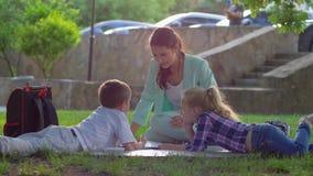 Мальчик с девушкой слушая женскую читая завораживающую книгу сидя на зеленой лужайке outdoors в солнечном свете позже сток-видео