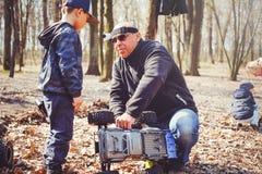 Мальчик с его отцом на моделях дороги контролируемых радио в природе, хобби и отдыхе Стоковые Изображения RF
