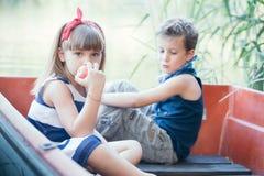 Мальчик с катанием девушки на шлюпке на озере Стоковая Фотография RF