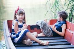 Мальчик с катанием девушки на шлюпке Стоковая Фотография RF