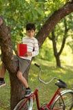 Мальчик с книгой сидит на дереве в саде и хитро уборной стоковое фото