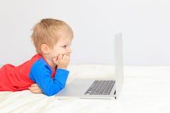 Мальчик с компьтер-книжкой дома стоковая фотография rf