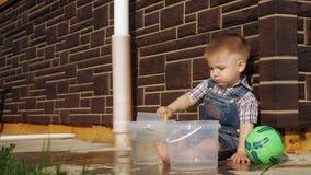 Мальчик с короткими светлыми волосами поливает воду из пластикового вРвидеоматериал
