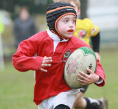 Мальчик с красным рэгби игры куртки Стоковые Изображения