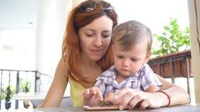 Мальчик с мамой использует интернет на smartphone видеоматериал