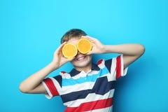 Мальчик с оранжевым плодоовощ стоковое фото