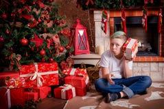 Мальчик с подарком сидит около рождественской елки Стоковые Изображения