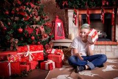 Мальчик с подарком сидит около рождественской елки Стоковые Фото
