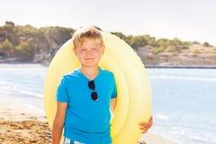 Мальчик с раздувным кольцом на пляже моря Стоковые Фотографии RF
